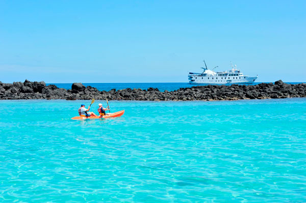 Kayakers on the water with La Pinta ship in the distance, Galapagos, Ecuador
