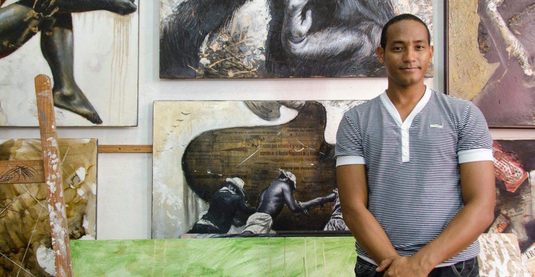 Artist standing before a wall of paintings, Havana Vieja, Havana, Cuba