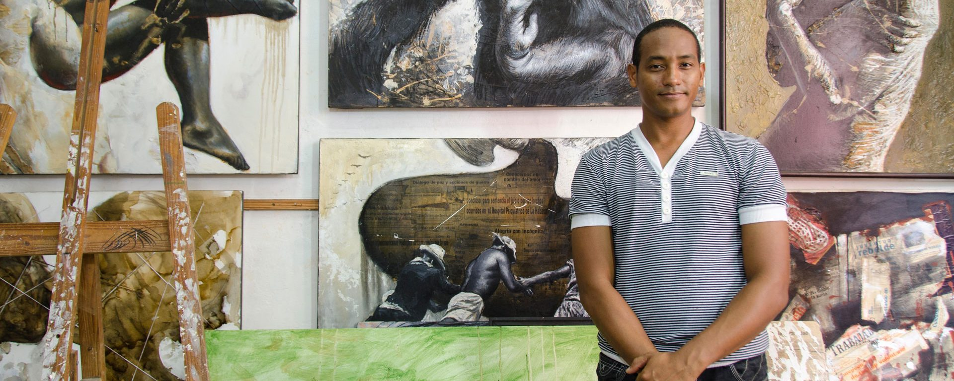 Artist standing before a wall of paintings, Havana Vieja, Havana, Cuba