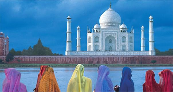 Colorful women standing in front of the Taj Mahal in India.