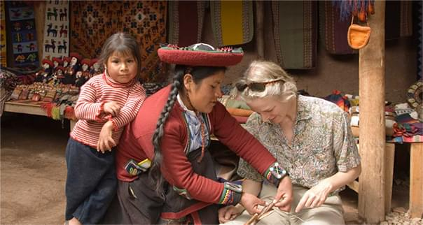 Mother and daughter showing tourist how to weave in Peru.