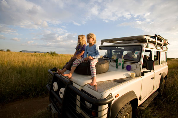 Young girls sit on the hood of their Land Rover as they look out over the game park, Masai Mara, Kenya