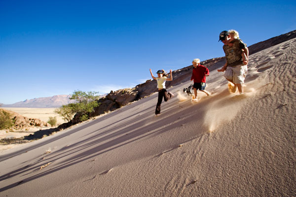 Family running down sand dunes on Brandberg Mountain, Namibia