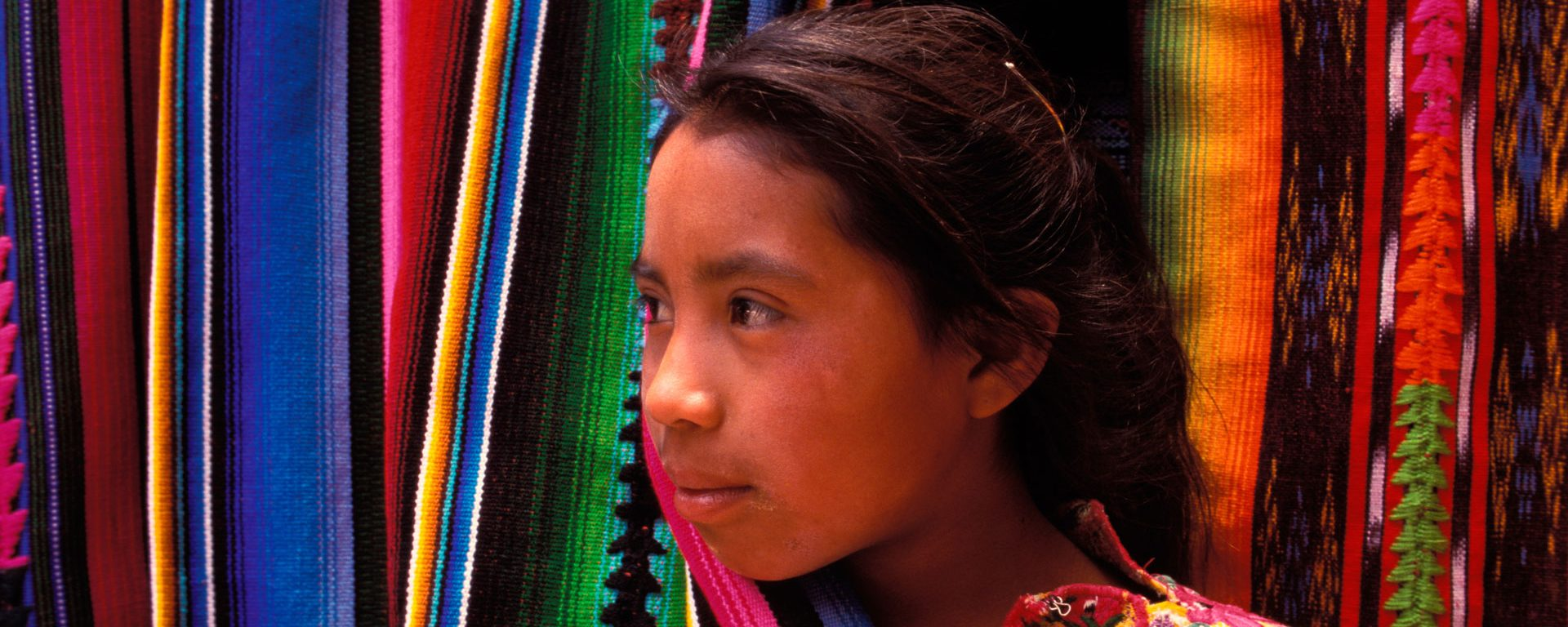 A girl peaks out from behind a colorful hanging blanket in Chichicastenango, Guatemala