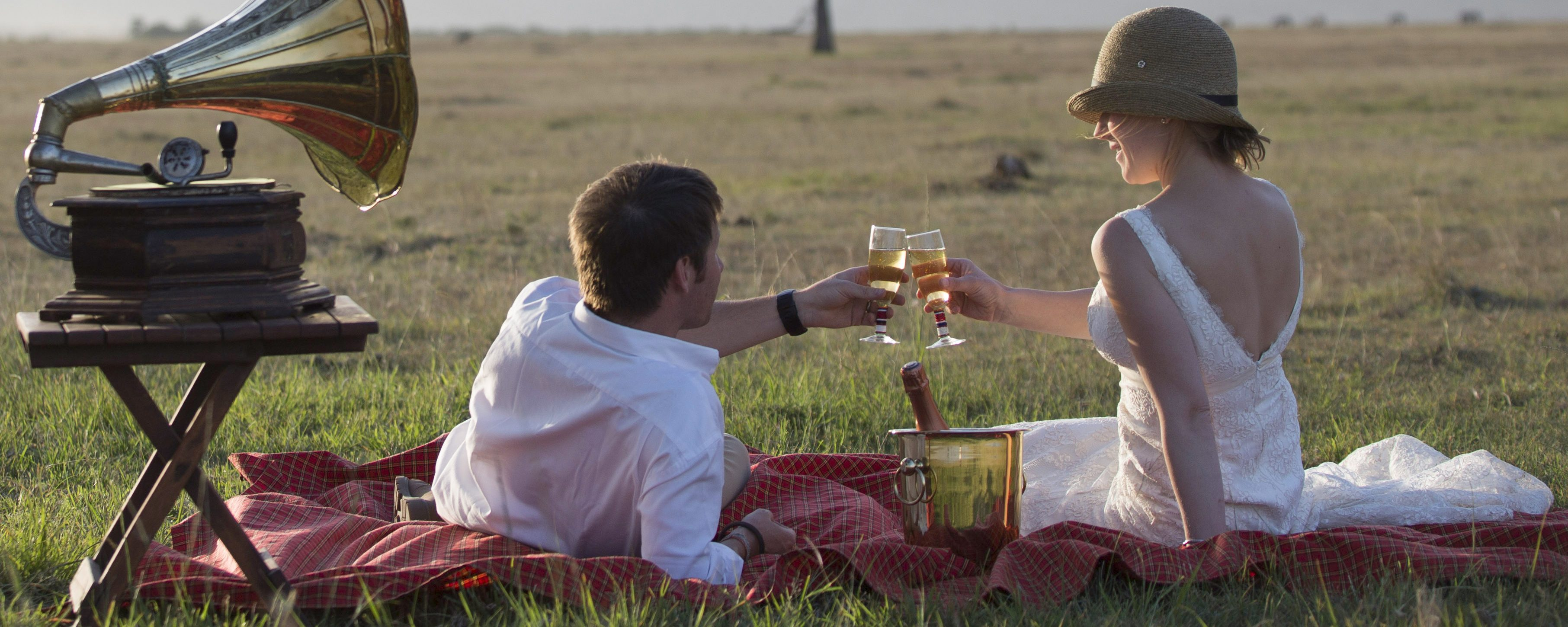 A newlywed couple toast with champagne in the Masai Mara, Kenya