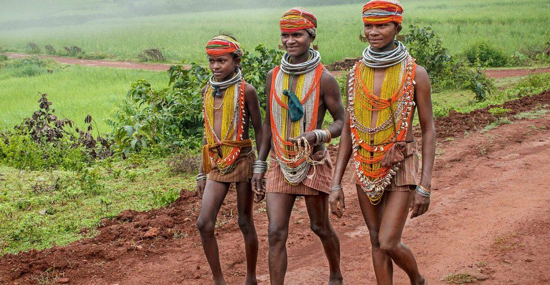 Three young Bonda women in beaded tribal dress walk down a red dirt road, India