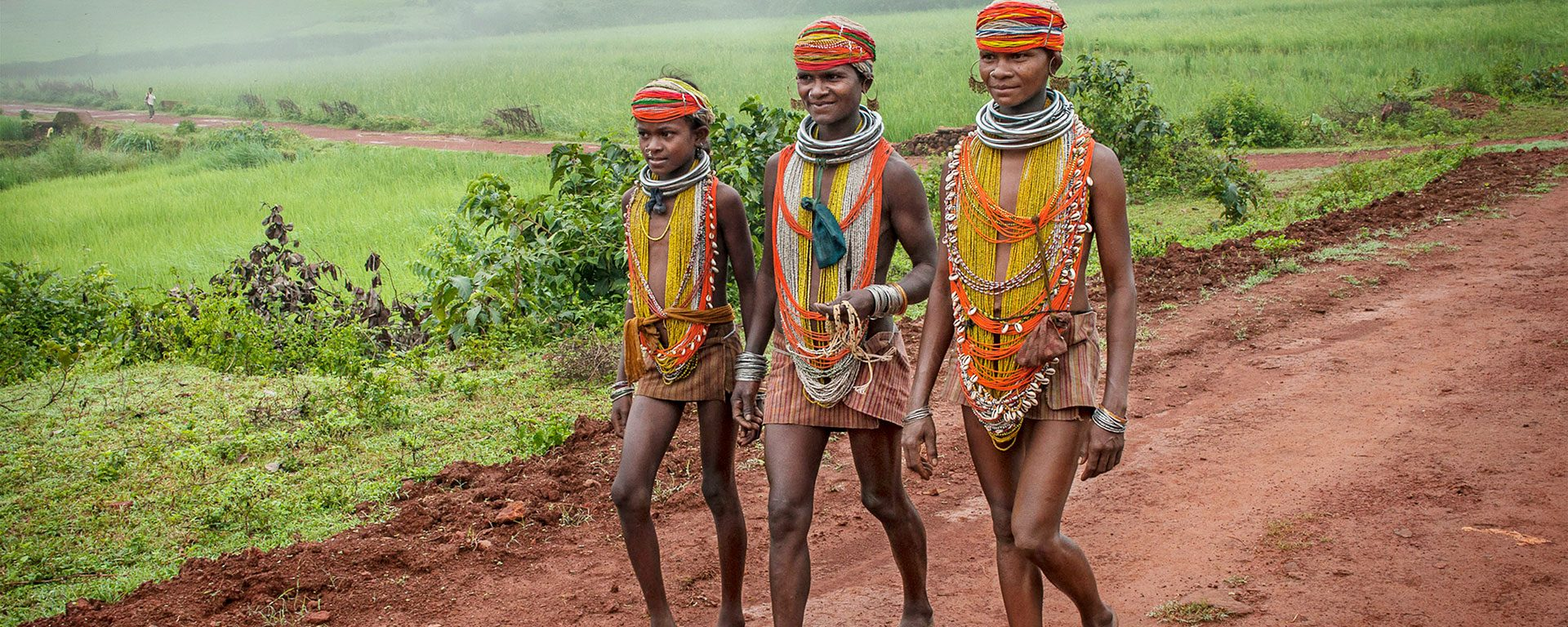 Three young Bonda women in beaded tribal dress walk down a red dirt road, India