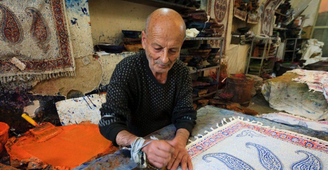 An artist crafts tapestries in his workshop, Iran