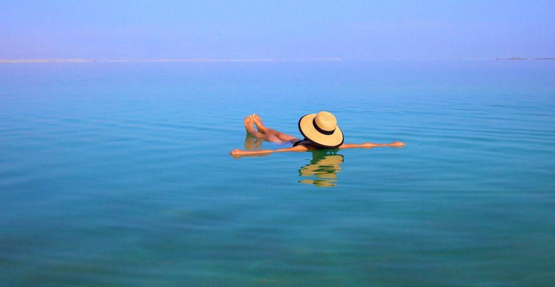 Woman with hat floating In The Dead Sea, Ein Bokek, Israel