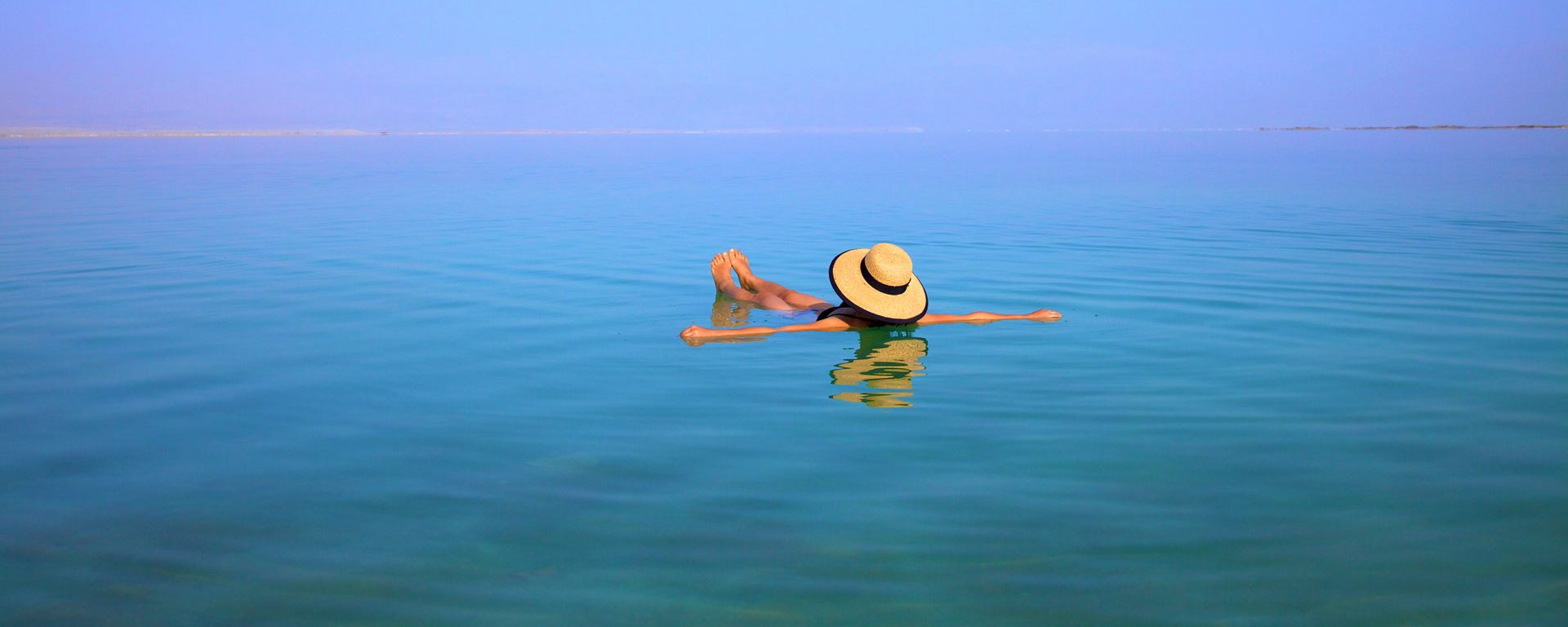 Woman with hat floating In The Dead Sea, Ein Bokek, Israel