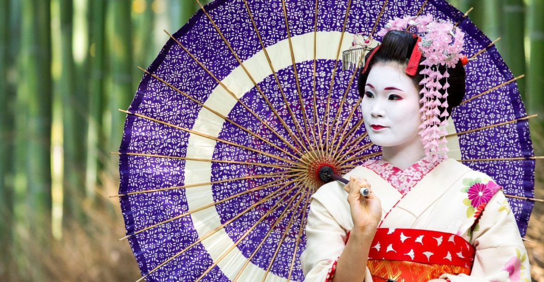 Maiko with colorful kimono and umbrella in Arashiyama, Kyoto, Japan