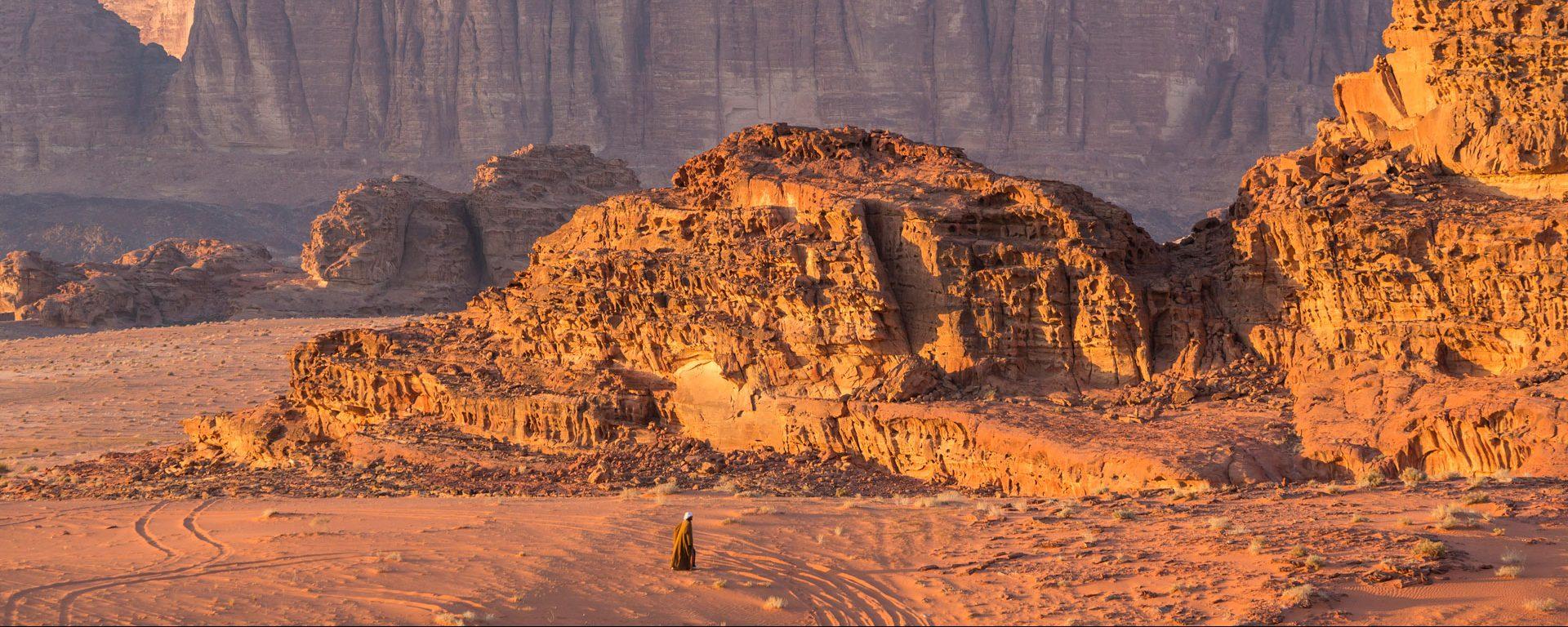 Bedouin man walking across desert, Wadi Rum, Jordan