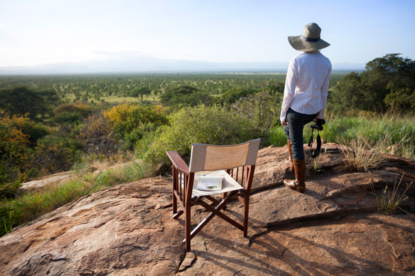 A young lady looks out over Meru National Park on safari in Kenya