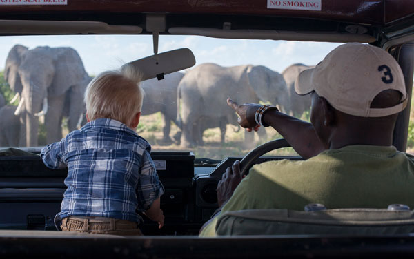 A small boy and his guide look at elephants through the windshield of their safari vehicle, Amboseli National Park, Kenya