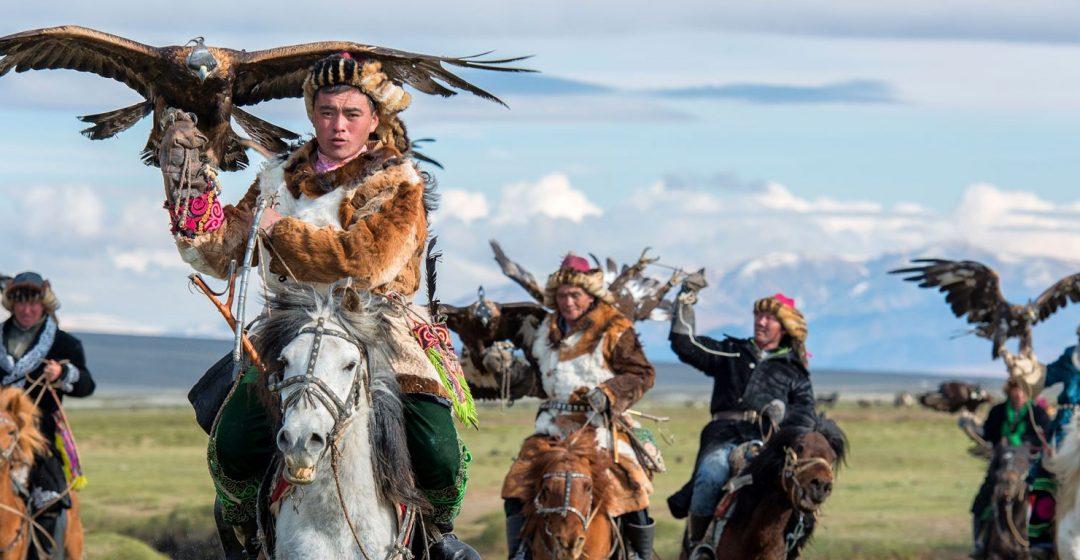 Kazakh eagle hunters on horseback in the the Altai mountains, Mongolia