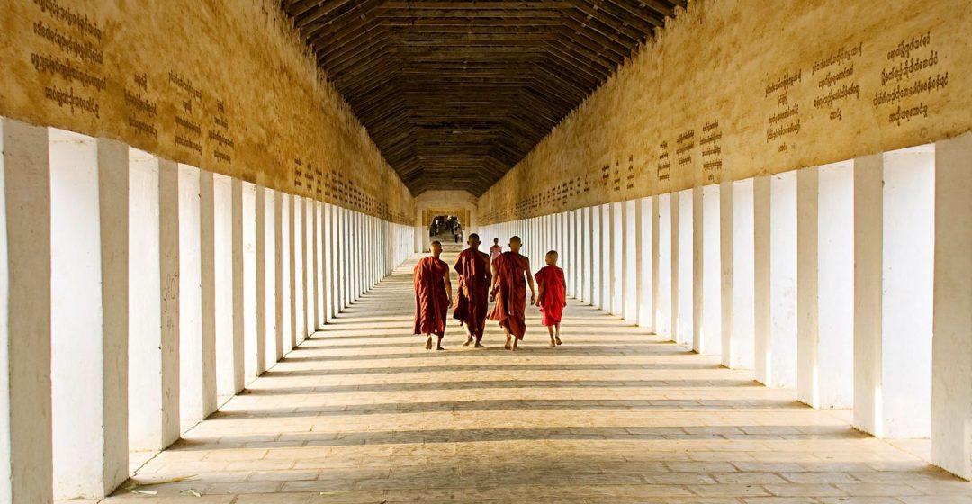 Young monks walking the hallway of Swezigon Pagoda near Bagan, Myanmar