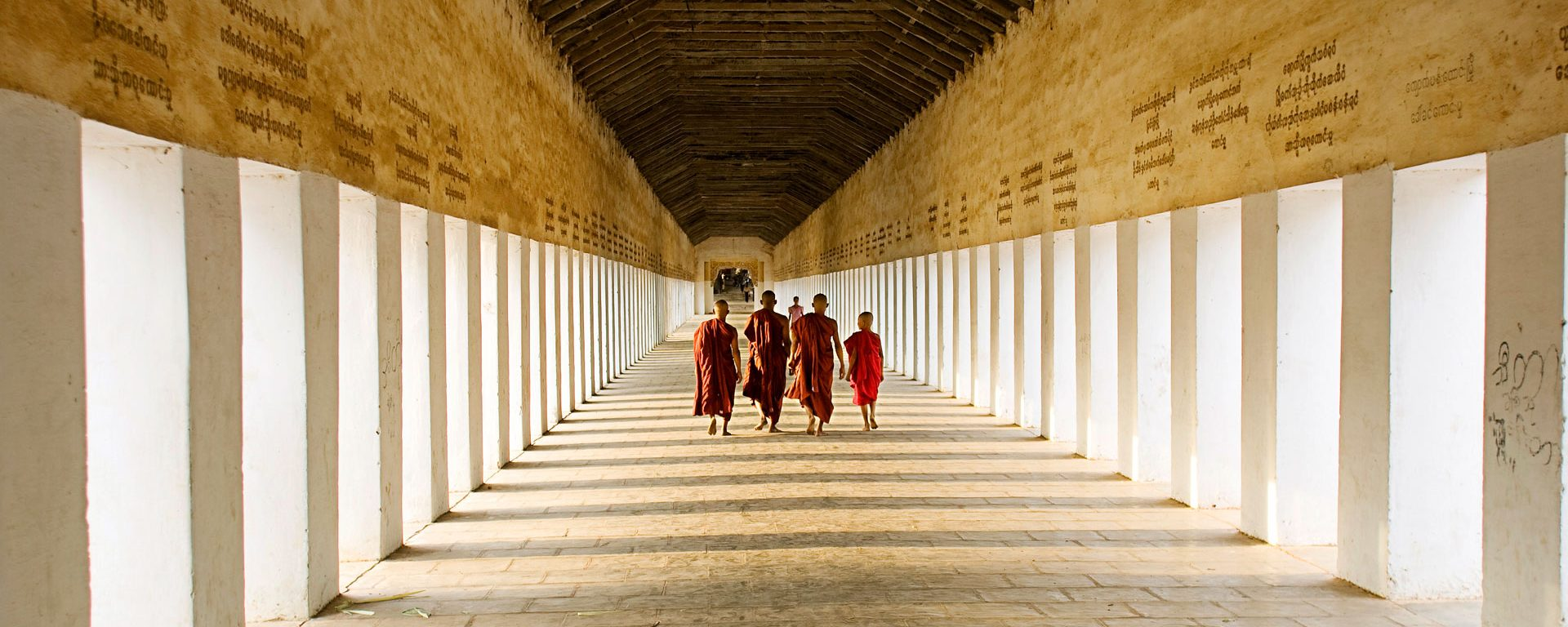 Young monks walking the hallway of Swezigon Pagoda near Bagan, Myanmar