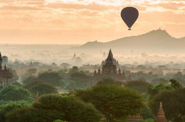 Hot air balloon flies over temples at dawn, Bagan, Myanmar
