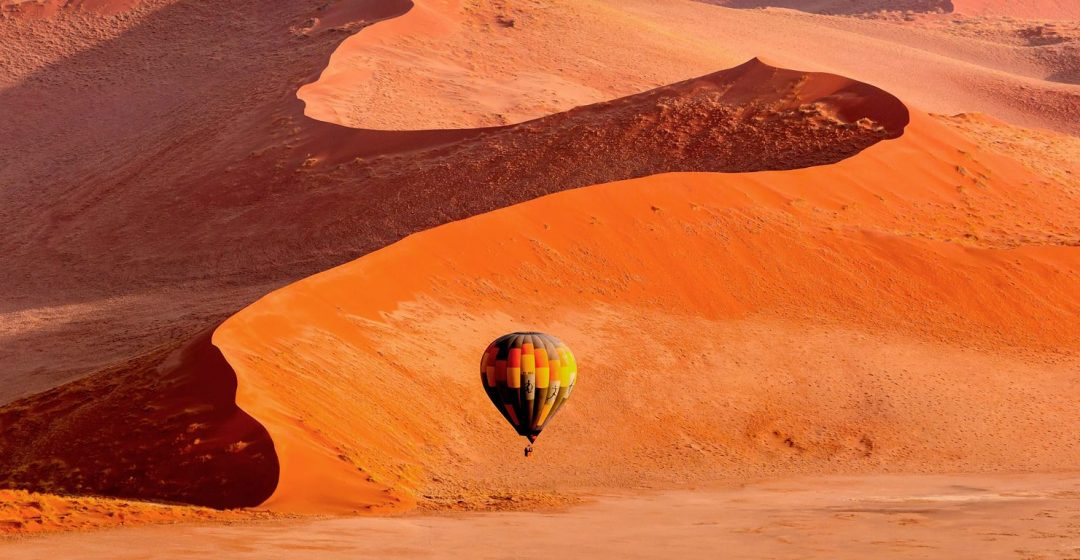 A hot air balloon floats across dunes in Namibia