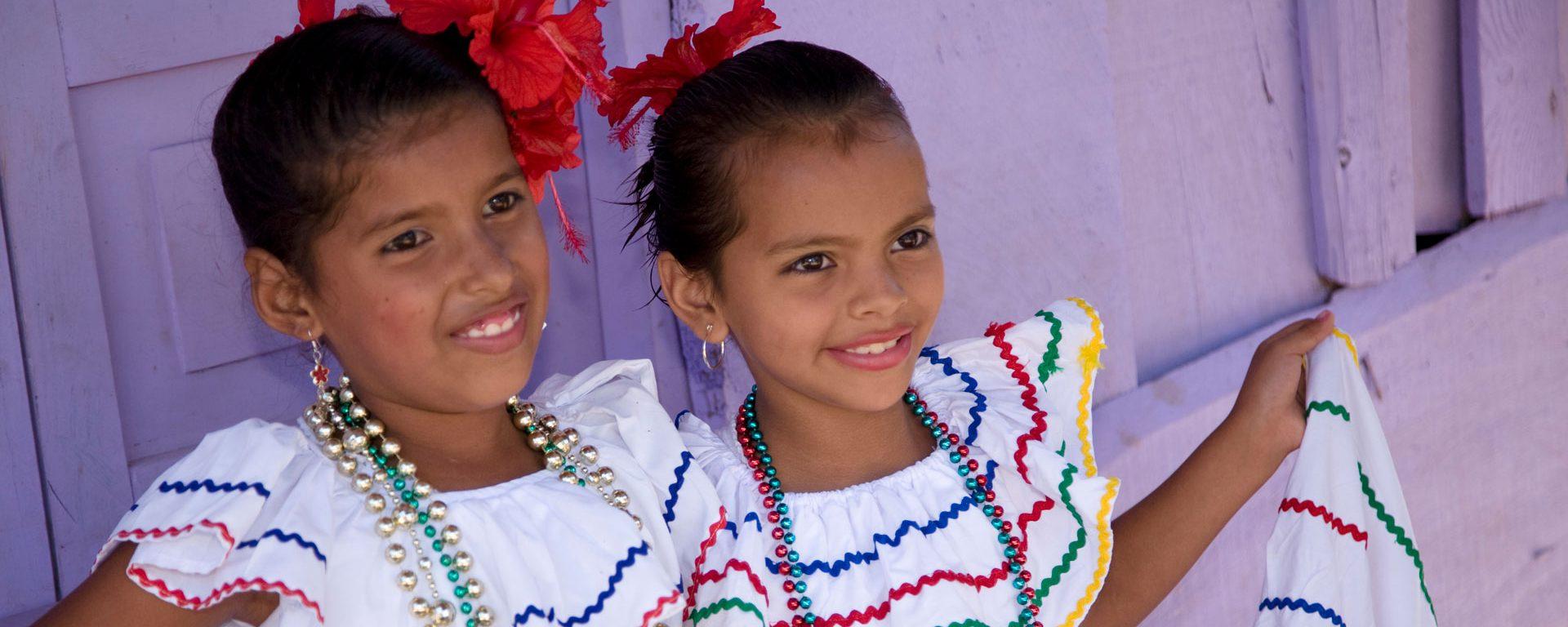 Girls in traditional dress after dance in Villa Esperanza barrio, Granada, Nicaragua