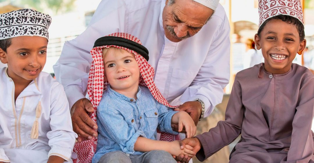 An Omani man helps a young European child shake hands with Omani children, Nizwa, Oman