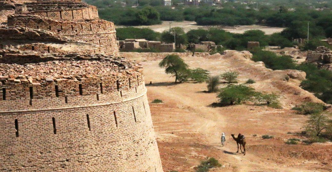 Man with camel walks outside Derawar Fort in Bahawalpur, Pakistan