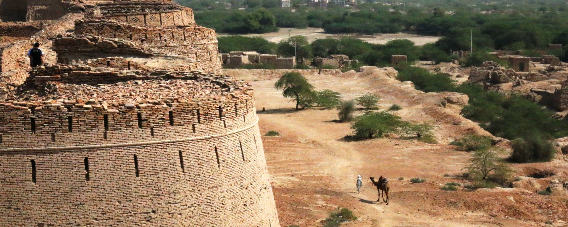 Man with camel walks outside Derawar Fort in Bahawalpur, Pakistan