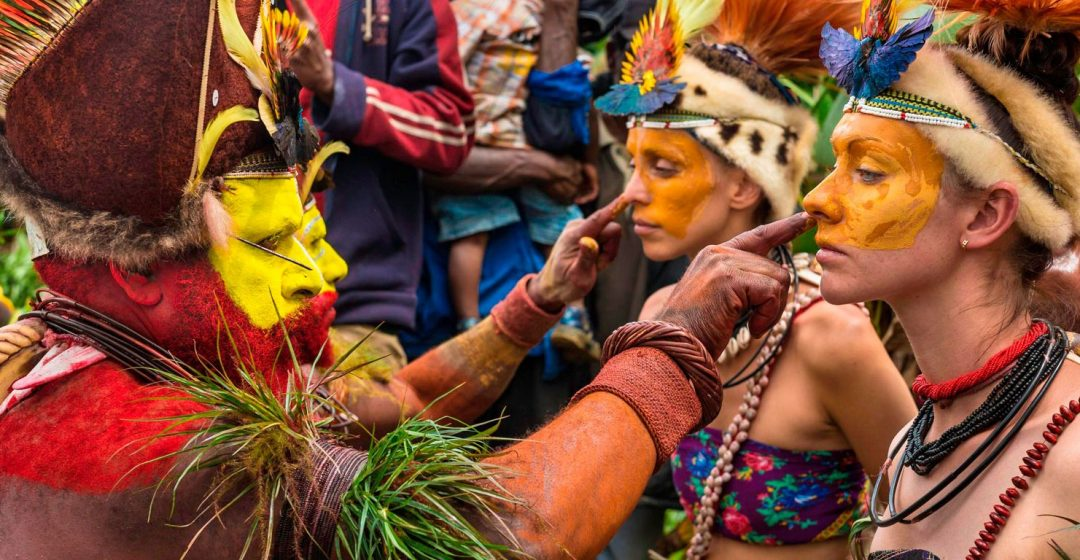 Tribesmen paint the faces of visitors during a traditional sing-sing in Papua New Guinea's Mount Hagen