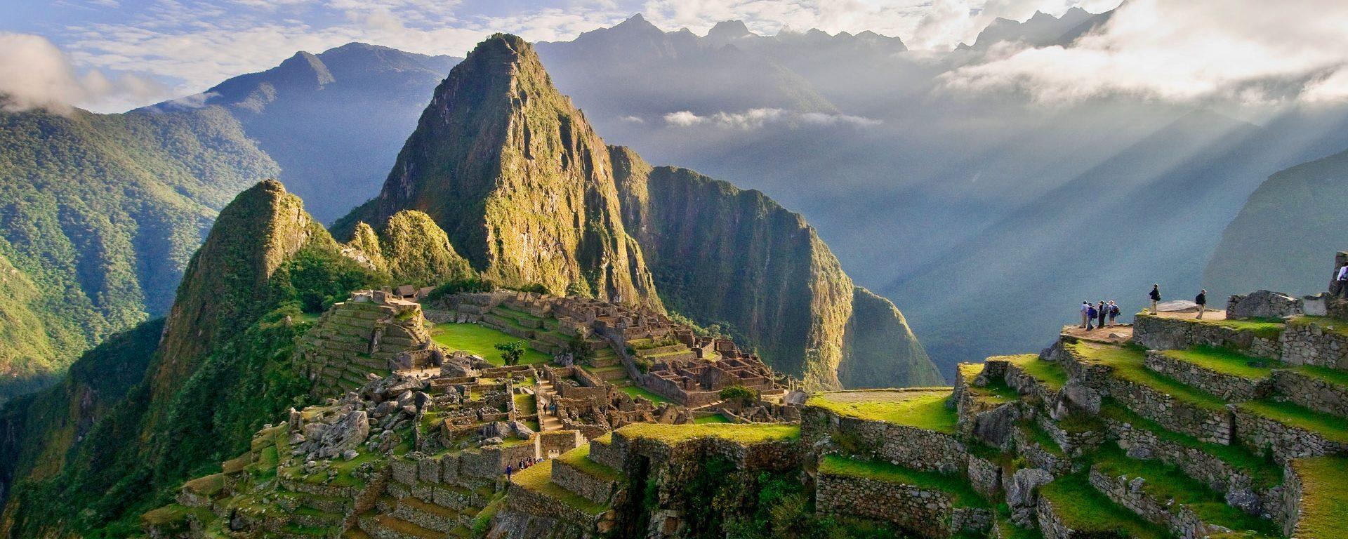 The suns rays break through the clouds illuminating Huayna Picchu, Machu Picchu, Peru