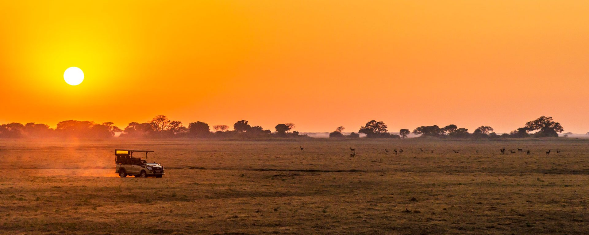 Safari vehicle at sunrise in Kafue National Park, Zambia