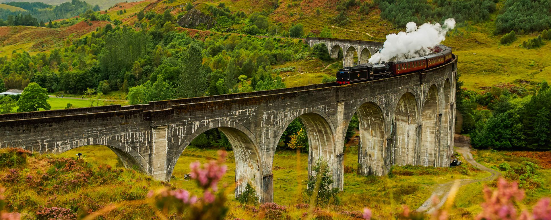 Jacobite Steam Train crossing the Glenfinnan Viaduct in Scotland, Highlands, UK