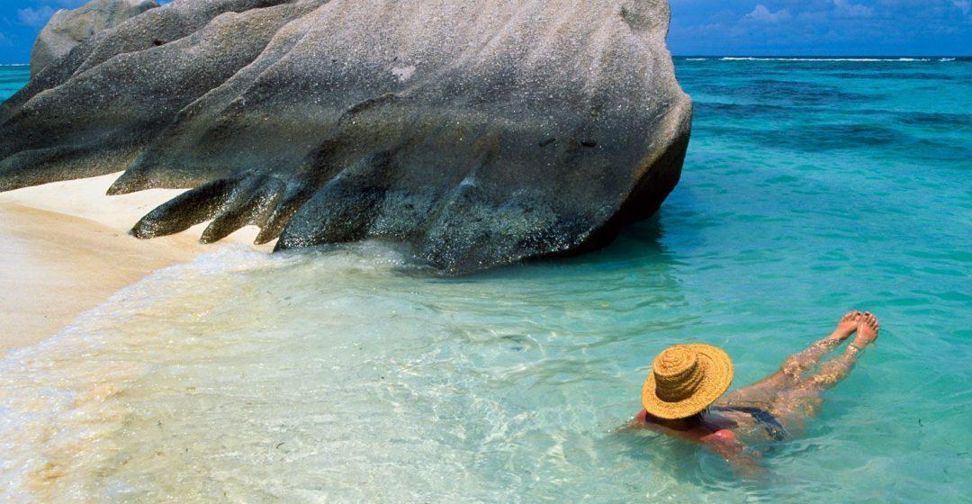 Woman swimming at beach on La Digue Island, Seychelles