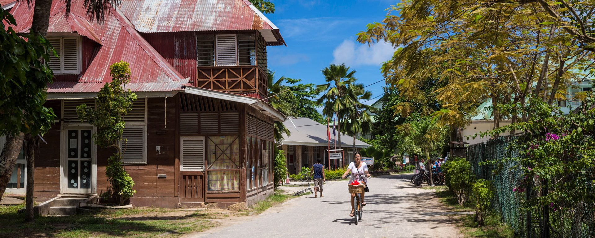 Woman rides bicycle in La Passe on La Digue Island, Seychelles