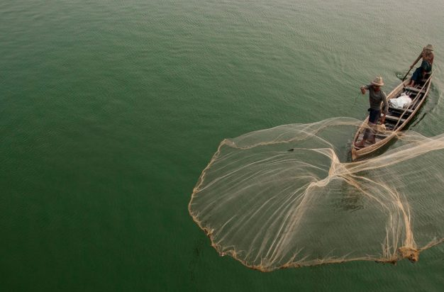 Myanmar, Mandalay, fisherman casting net on Irrawaddy River