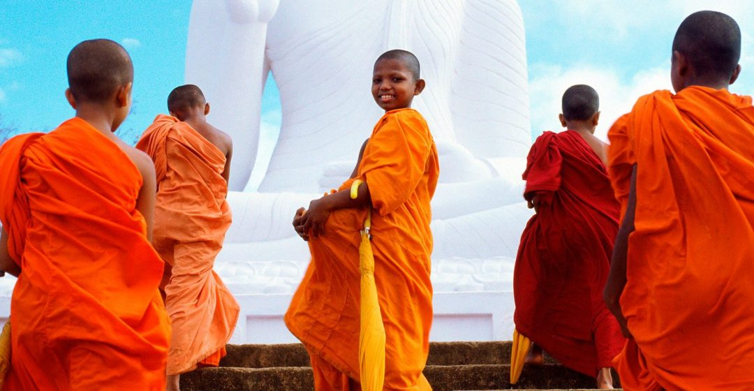 Group of young monks walking up steps in front of Buddha statue in Mihintale, Sri Lanka