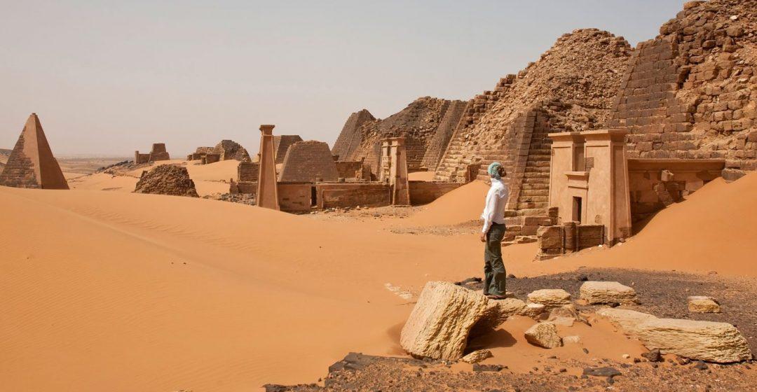 Woman explores ancient Nubian pyramids in Begrawiya, Sudan