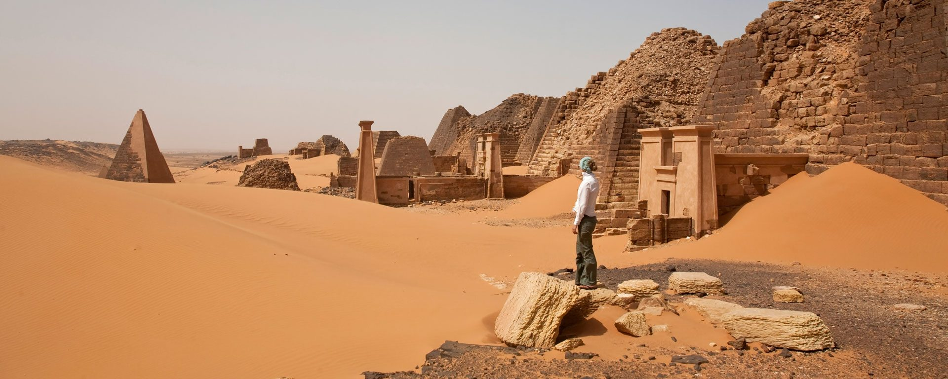 Woman explores ancient Nubian pyramids in Begrawiya, Sudan