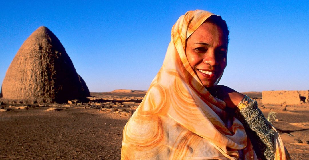 Nubian woman in front of domed structures in Old Dongola, Sudan