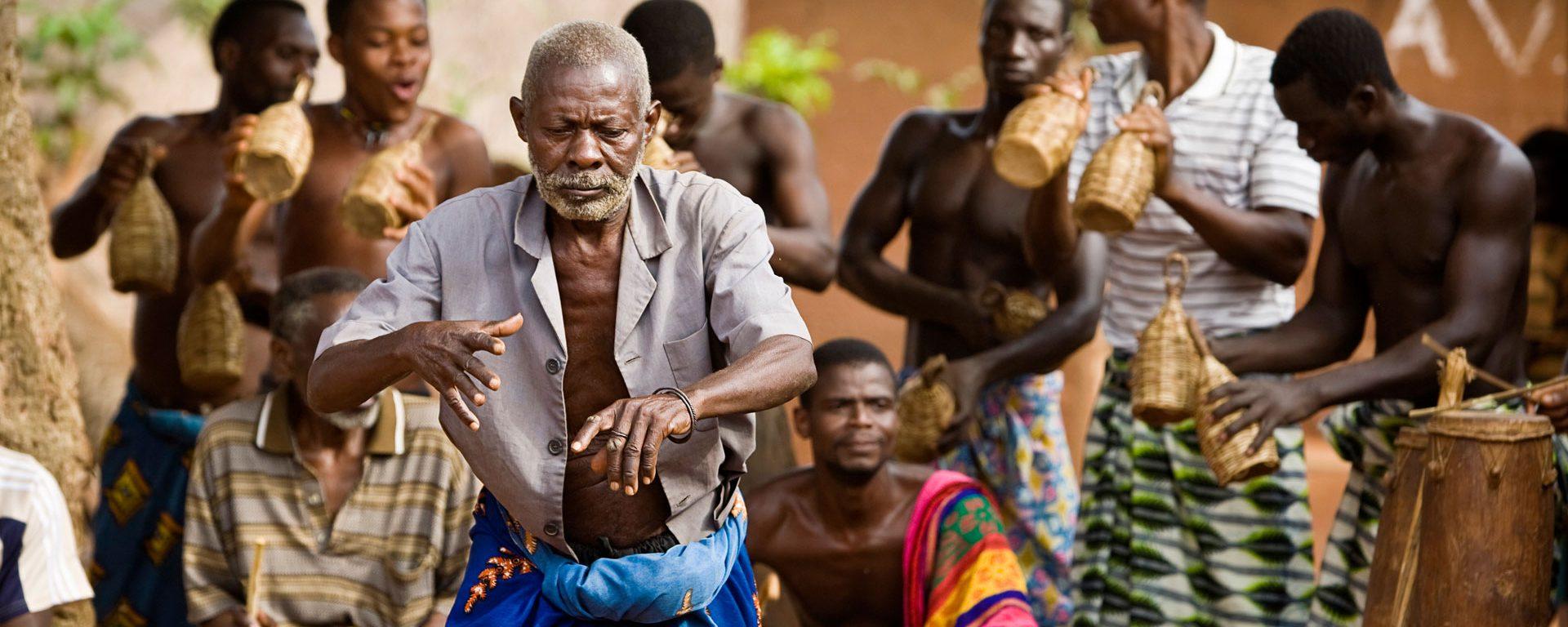Village elder dancing with drummers during voodoo ceremony in Atitogan, Togo