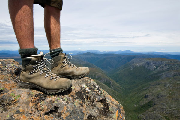 Feet-only view of hiker standing on the summit of Cradle Mountain, Tasmania, Australia