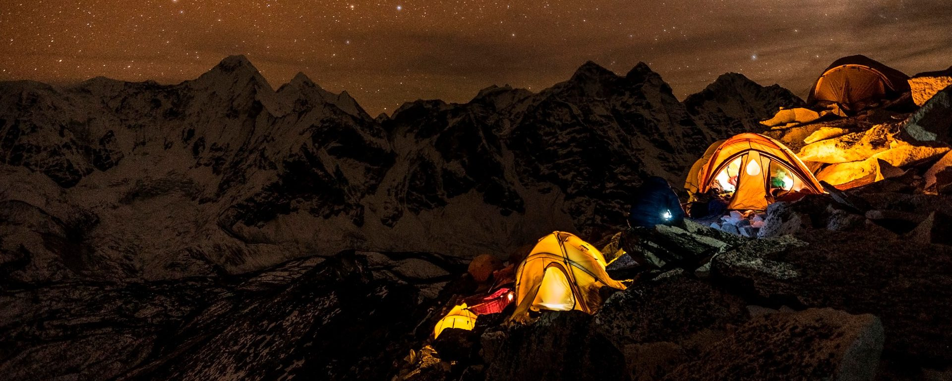 Trekking tents glowing against the night sky with mountains in the distance