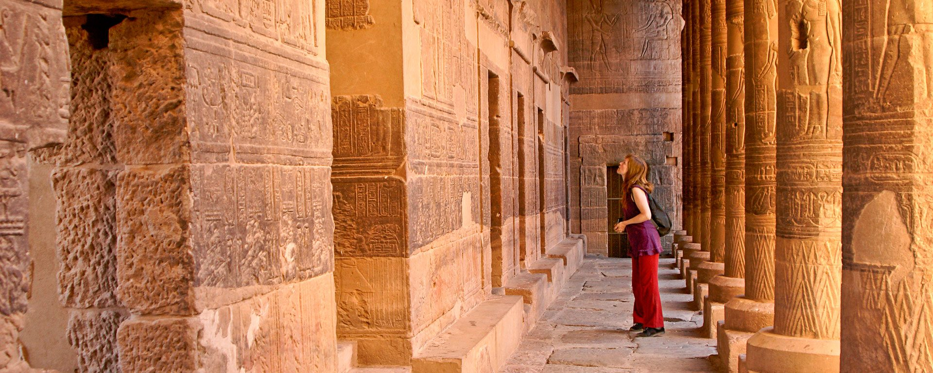 Female traveler in colonnade at Philae Temple, Aswan, Egypt