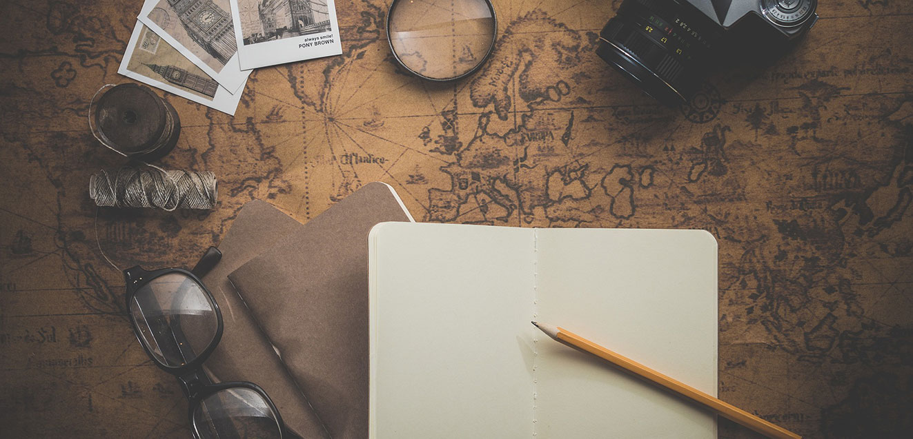 A collection of travel-themed items laid out on an old sepia map. Open notebook and pencil are predominantly featured.