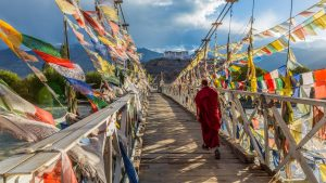 A monk walks across a bridge covered in prayer flags in Leh, in the Ladakh region of India