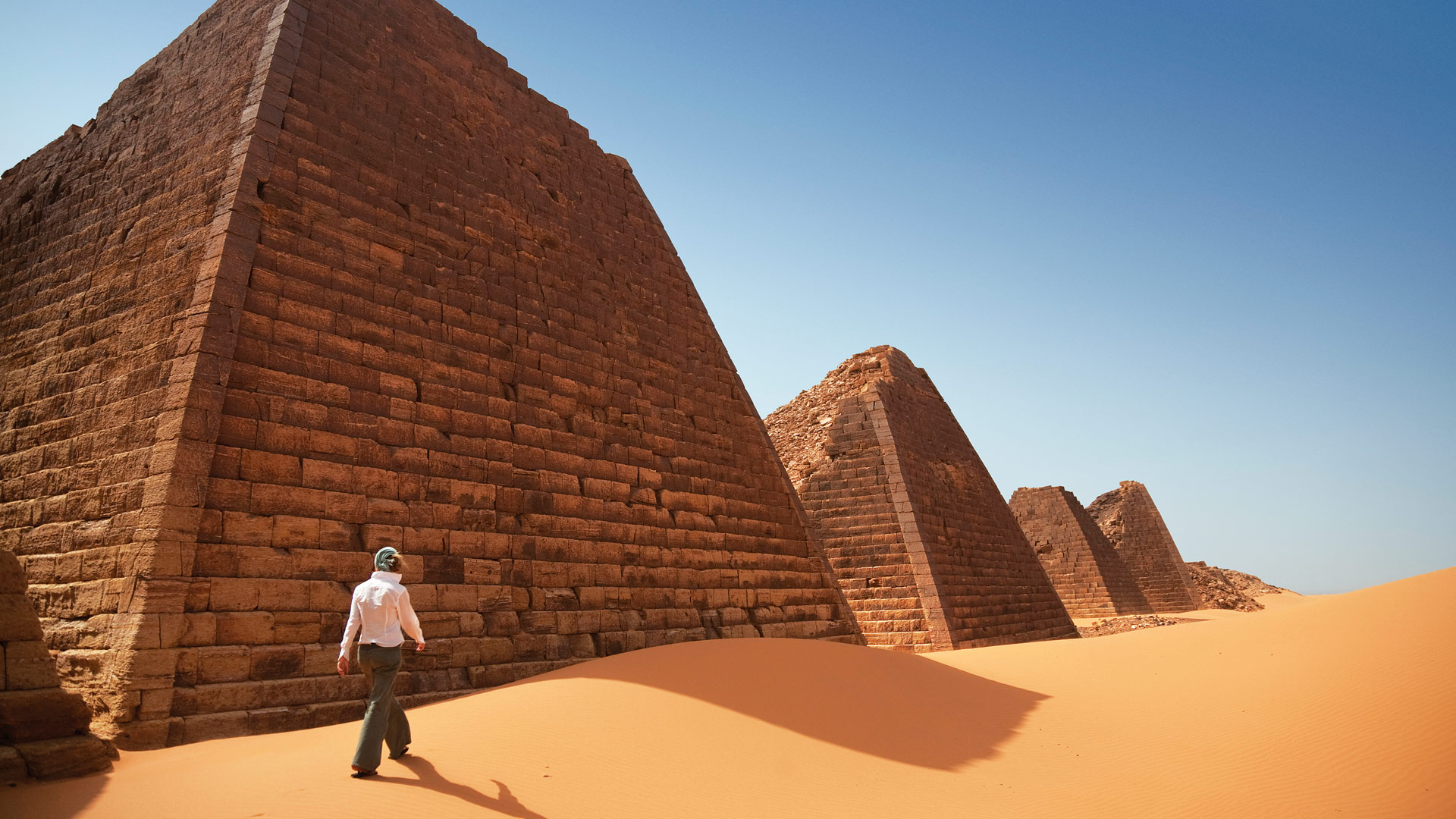 A woman explores the ancient Nubian pyramids of Begrawiya, Sudan