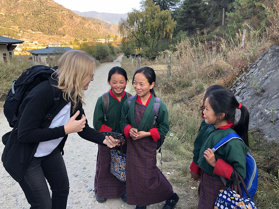 A female traveler interacts with schoolgirls on a walking path in Bhutan.