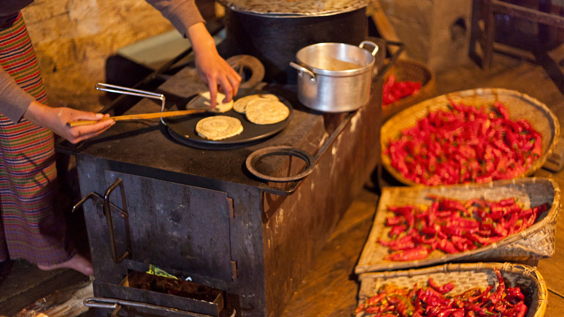 Woman preparing pancakes in a kitchen in Bhutan