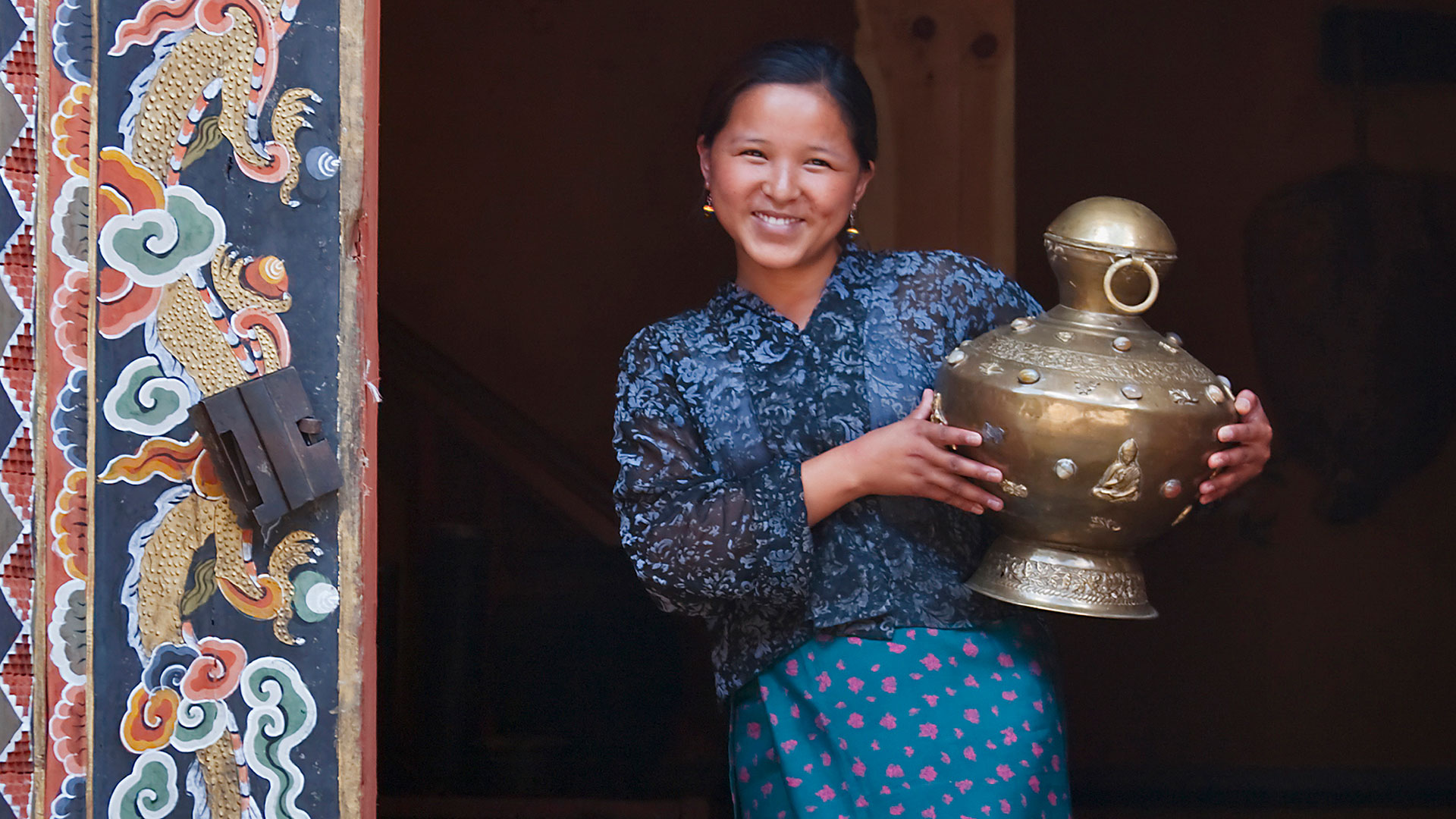 Girl holding water jar by decorated doorway of a traditional house in Paro, Bhutan
