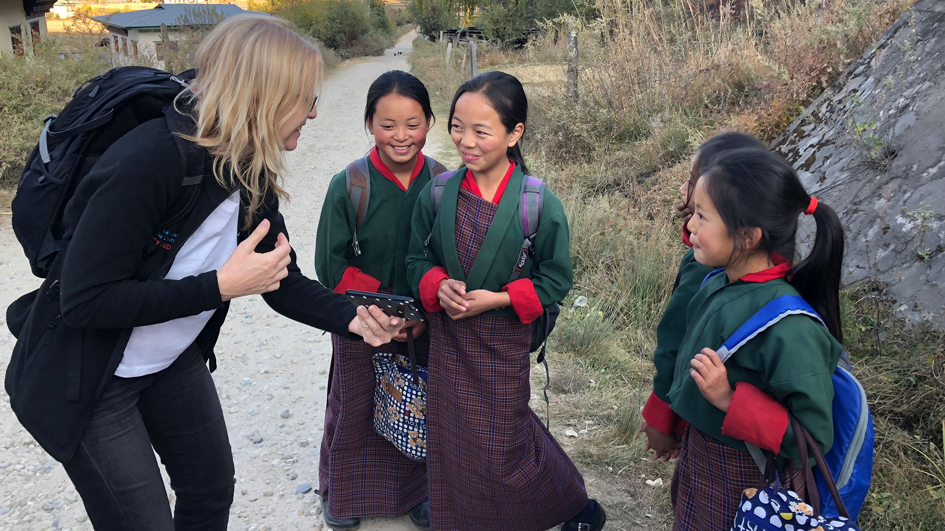 A woman interacts with local school girls in Bhutan