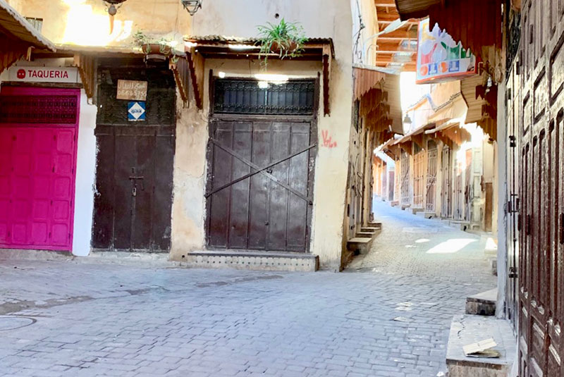 An empty town square and alleyway in Fez, Morocco, early morning.